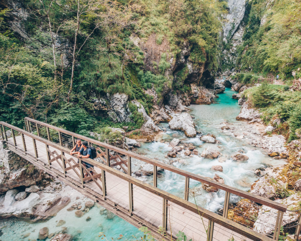 travel couple on the bridge at Tolmin Gorge in Slovenia