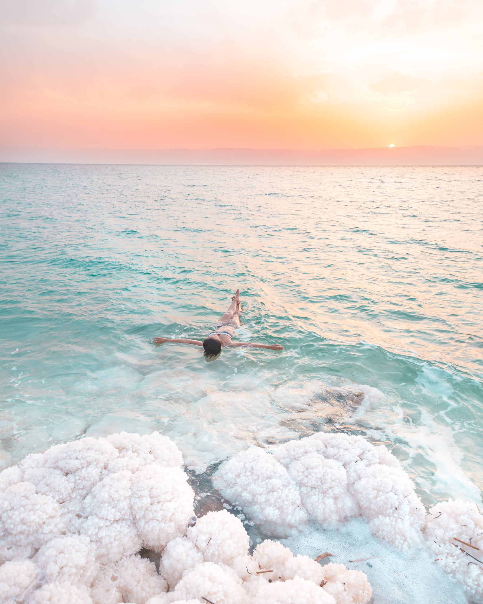 Woman floating in the dead sea Jordan during sunset