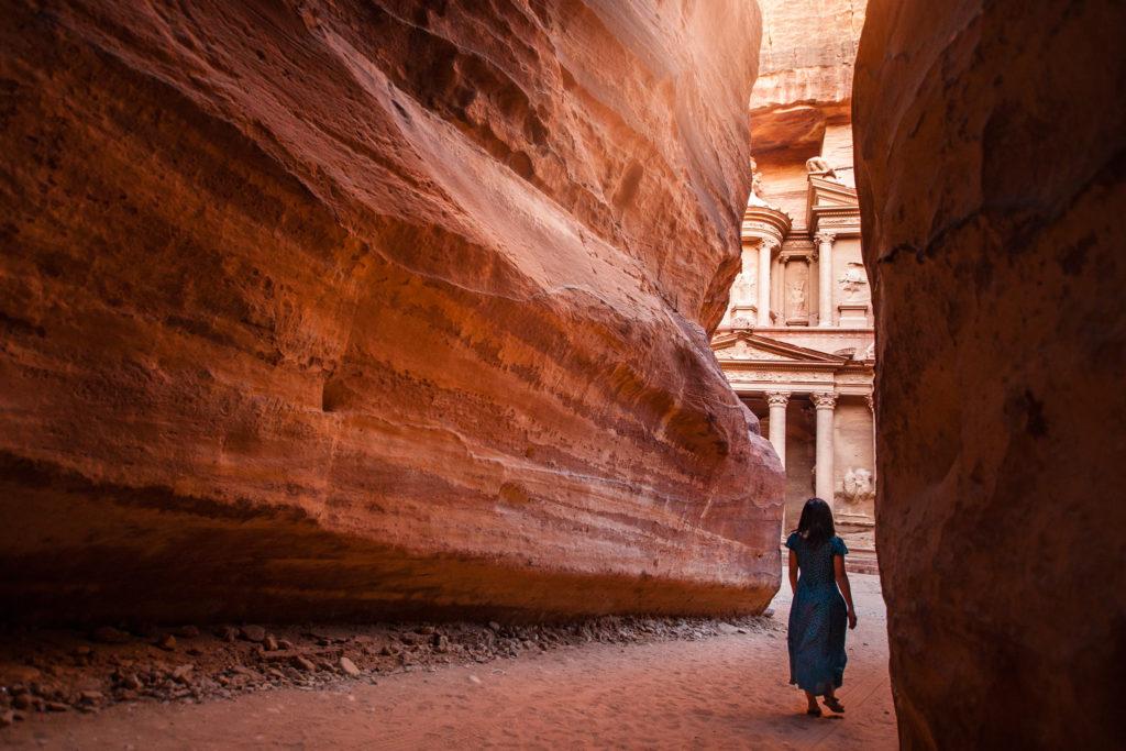 Woman walking through canyon towards Treasury at Petra in Jordan