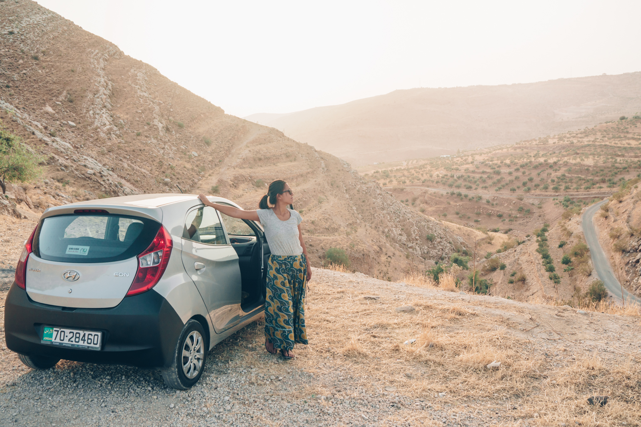 Woman standing next to silver car overlooking Jordan valley and mountains