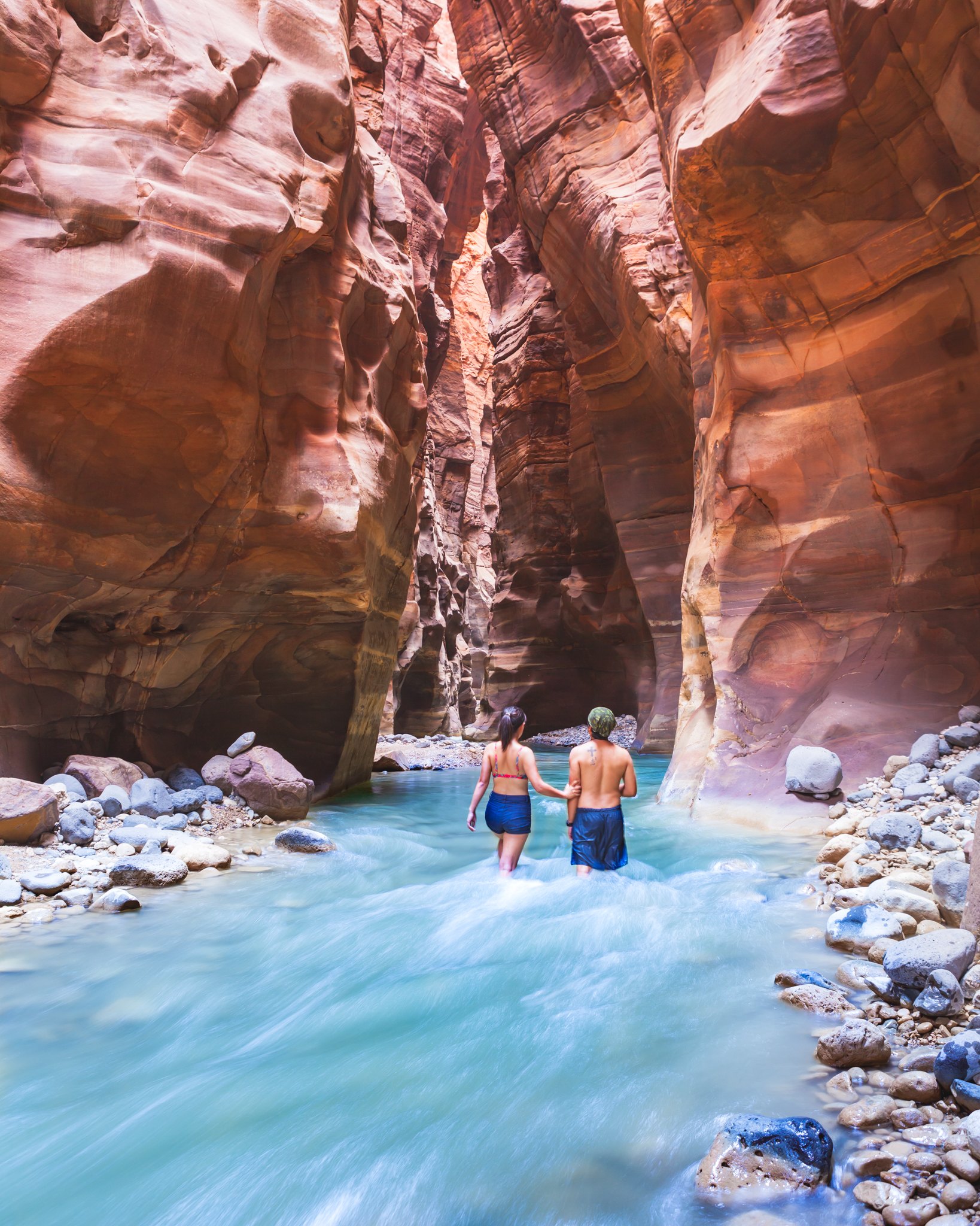 Travel couple walking in the Wadi Mujib Water through the high rock walled canyon